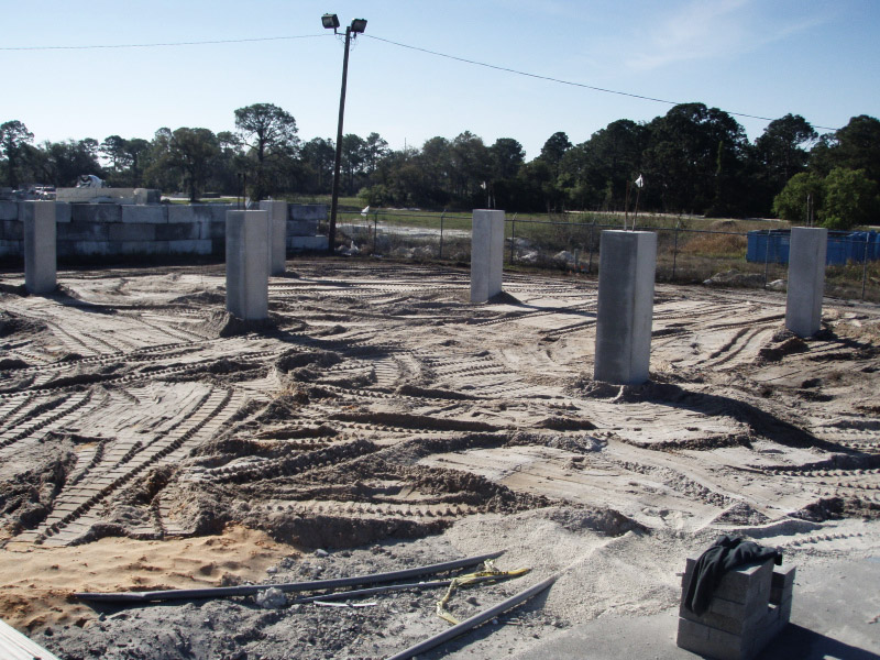 Rough grading covers subsurface foundation grade beams in preparation for assembly.